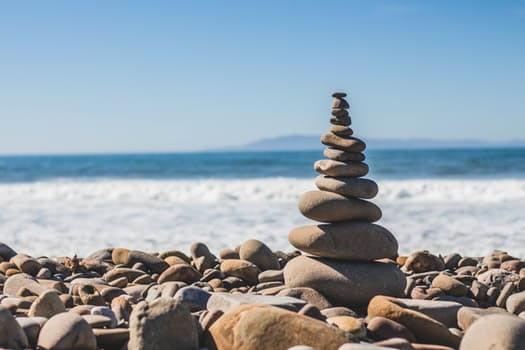 calming tower of balanced stones on the side of the ocean